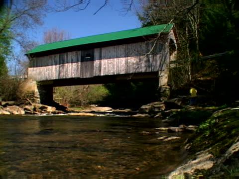 vídeos y material grabado en eventos de stock de boy throwing rocks in creek below covered bridge - artbeats