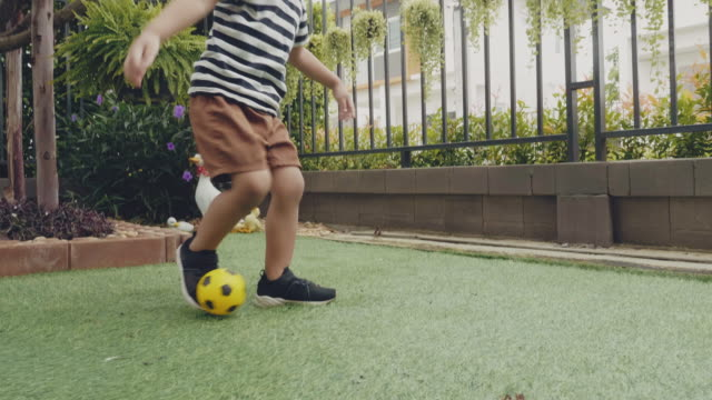 boy throws up and kick the ball, running on green lawn - sporting term stock videos & royalty-free footage