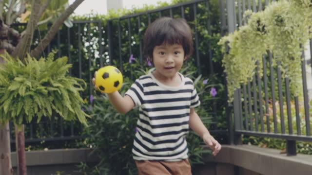 vidéos et rushes de le garçon jette vers le haut et donne le coup de pied la bille, fonctionnant sur la pelouse verte - aire de jeux