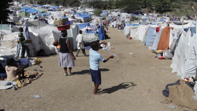 a boy tries to fly a kite in a haitian post earthquake tent camp. - haiti stock videos & royalty-free footage