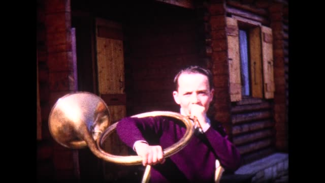 1965 boy tries to play early swiss hunting horn, girl interferes - french horn stock videos and b-roll footage