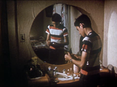 1955 boy trying on mother's lipstick in front of vanity mirror / getting upset and wiping off lipstick