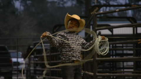 boy twirls lasso at rodeo grounds - rodeo stock videos & royalty-free footage