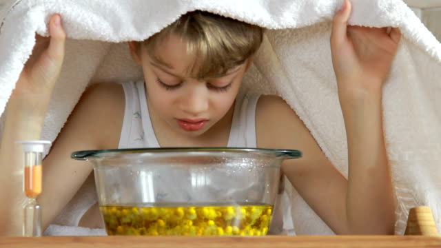 boy under towel breathes balsam vapors to treat colds