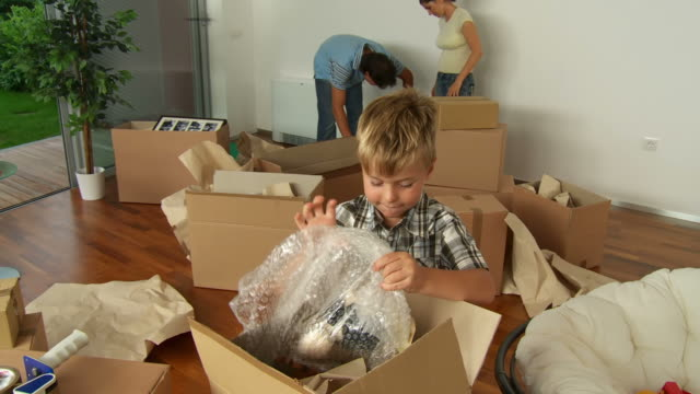 hd: boy unpacking toys in new home - relocation stock videos & royalty-free footage