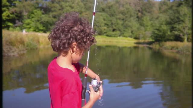 ms, boy (8-9) untangling fishing reel by lake, bovina, new york state, usa - gelockt stock-videos und b-roll-filmmaterial