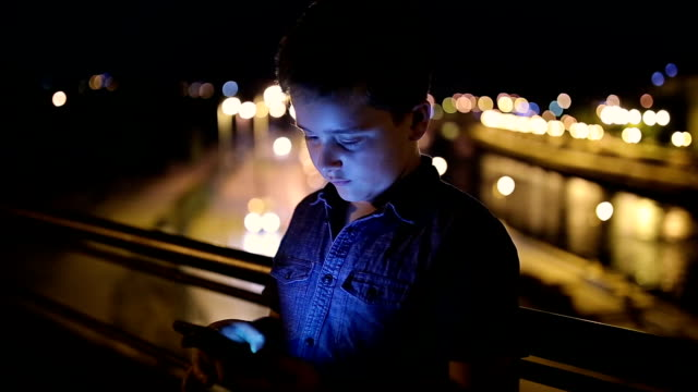 boy using a mobile phone at night - human face photos stock videos & royalty-free footage
