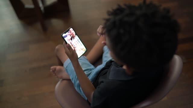 vídeos de stock, filmes e b-roll de menino usando um smartphone para fazer uma chamada de vídeo com sua mãe - distante