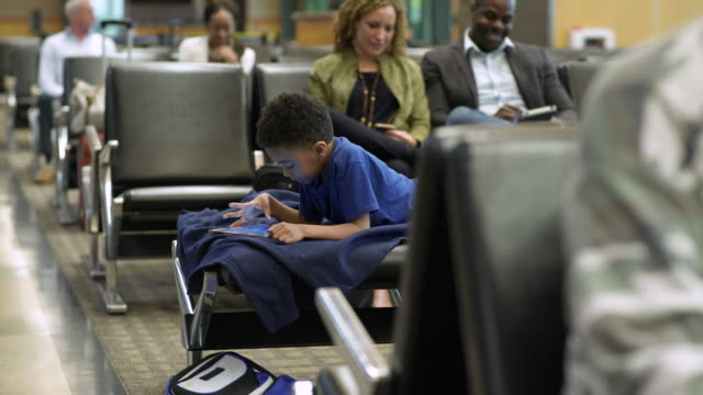 Boy using a tablet at an airport