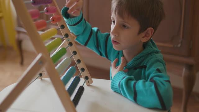 Boy using abacus, handheld shot