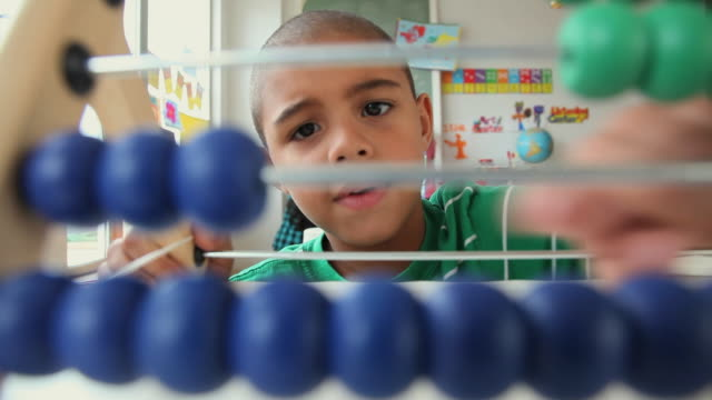 CU SELECTIVE FOCUS Boy (6-7) using abacus in classroom / Jersey City, New Jersey State, USA