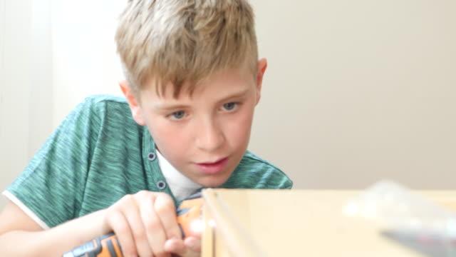 stockvideo's en b-roll-footage met boy using cordless screwdriver for preparing toy kitchen at home - alleen jongens