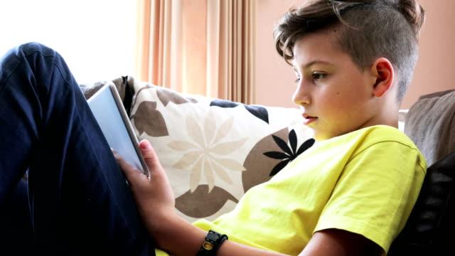 boy using digital tablet at home - un ragazzo adolescente video stock e b–roll