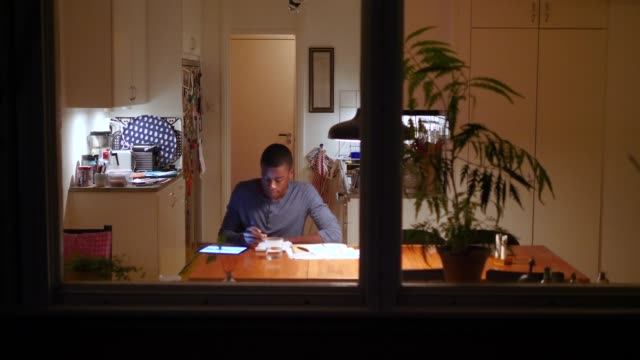 vídeos de stock e filmes b-roll de boy using digital tablet for doing homework at illuminated table against kitchen - 12 13 anos