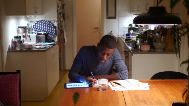 boy using digital tablet for doing homework at illuminated table against kitchen - pendant light stock videos & royalty-free footage