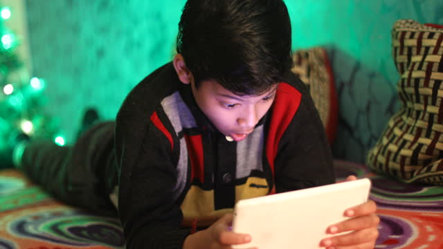 boy using digital tablet lying on bed - lying on front stock videos & royalty-free footage