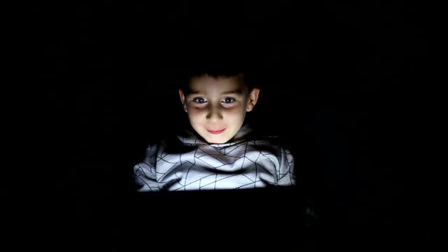 デジタル タブレットを使用してベッドの上の少年 - 驚き点の映像素材/bロール