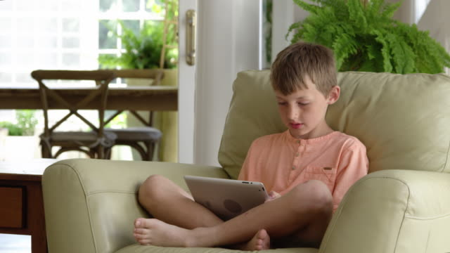 boy using digital tablet sitting on armchair - 8 9 år bildbanksvideor och videomaterial från bakom kulisserna