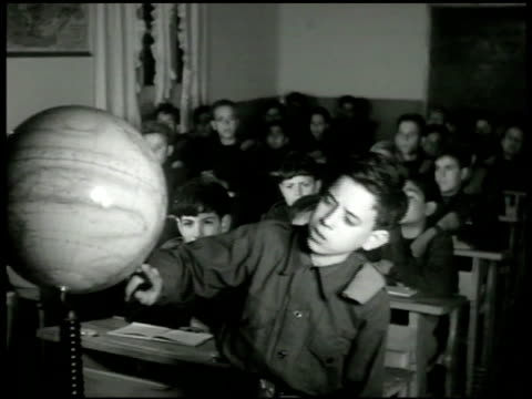 stockvideo's en b-roll-footage met boy using globe in classroom geography. boys seated at desks. boy standing at front of class using globe south american map in front of seated... - fysische geografie