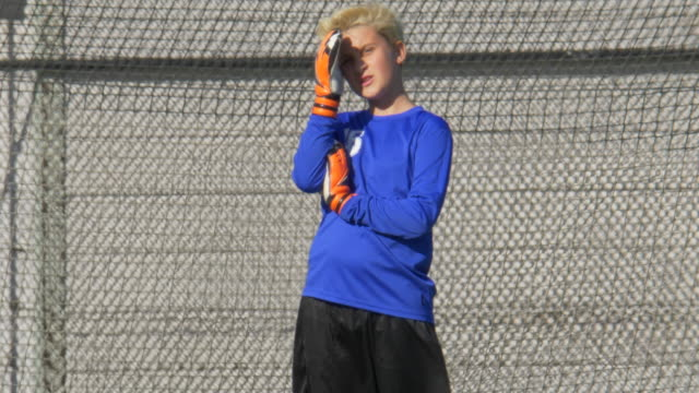 a boy using his hand as a visor to block the sun for youth soccer football goalie goalkeeper on a turf grass field. - slow motion - sun visor stock videos and b-roll footage