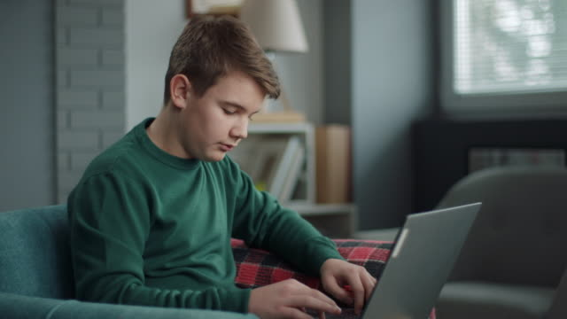 boy using laptop for homework - teenage boys stock videos & royalty-free footage