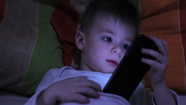 junge mit telefon in der nacht - erzählen stock-videos und b-roll-filmmaterial