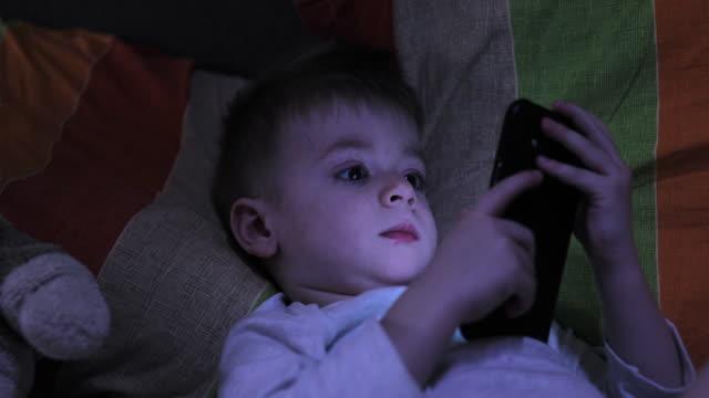 vídeos de stock, filmes e b-roll de menino que usa o telefone na cama - só um bebê menino