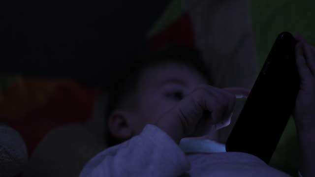 vídeos de stock, filmes e b-roll de menino que usa o telefone na cama - bebês meninos