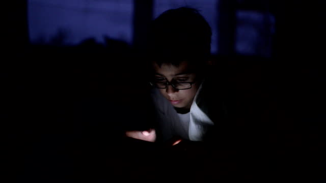 boy using smart phone in bed at night - bambini maschi video stock e b–roll