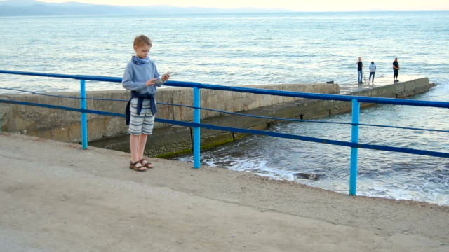 boy using smart phone - embankment stock videos and b-roll footage