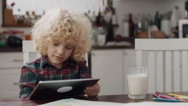 vidéos et rushes de garçon utilisant la tablette - équipement informatique