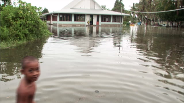 vídeos de stock, filmes e b-roll de boy wades through flood water in plaza in front of government building tuvalu - vadear