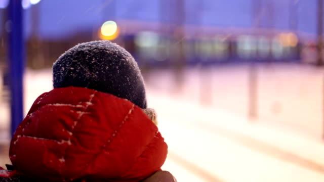 vidéos et rushes de garçon en attente pour le tramway, hiver, neige - ligne de tramway