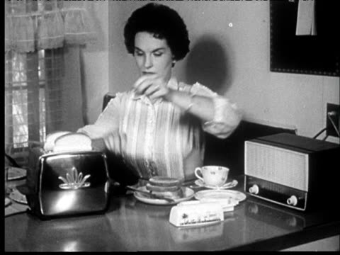 1958 b/w boy wakes up, gets out of bed/woman makes toast/ man uses electric shaver/family eats breakfast and listens to radio/father and son leave house/kissed by mother - 1950~1959年点の映像素材/bロール