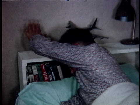 montage cu boy waking up and turning off alarm clock / ms boy stretching and yawning in bed / usa - pigiama video stock e b–roll