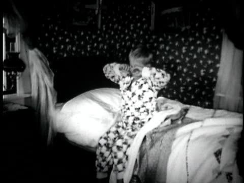 B/W MS Boy waking up, rubbing his eyes, and stretching in bed / Knights Ferry, California, USA