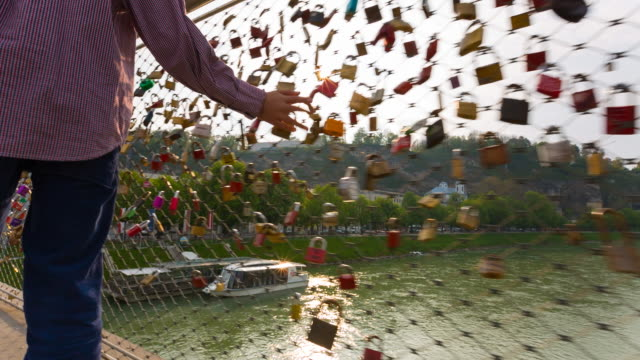vídeos y material grabado en eventos de stock de boy walking across bridge adorned with padlocks symbolising love - oportunidad