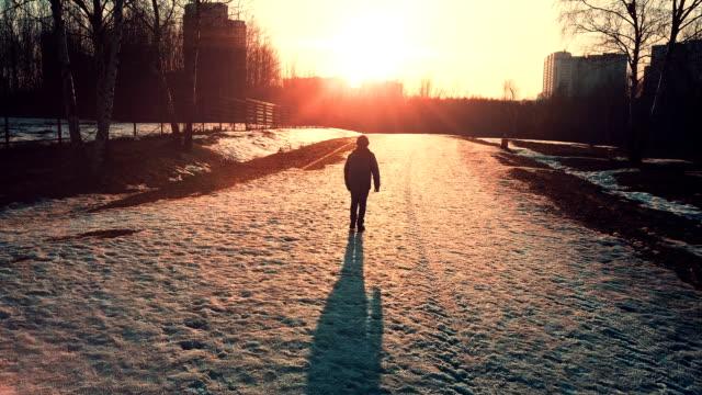 Un garçon à marcher seul dans le parc au coucher du soleil