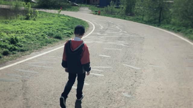 stockvideo's en b-roll-footage met jongen lopen alleen in het park - de volgende stap