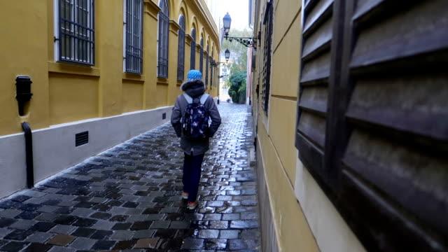 stockvideo's en b-roll-footage met jongen wandelen alleen op een geplaveide straat met een rugzak - stock video - hongarije