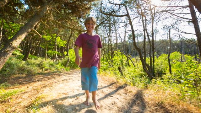 Boy walking barefoot along sandy track through pine forest, steady cam