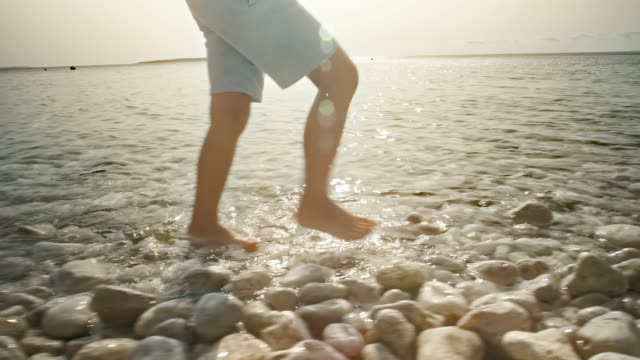 boy walking in shallow water on round rocks in sunshine - shorts stock videos & royalty-free footage