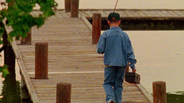 Boy walking on dock with fishing pole + tackle box
