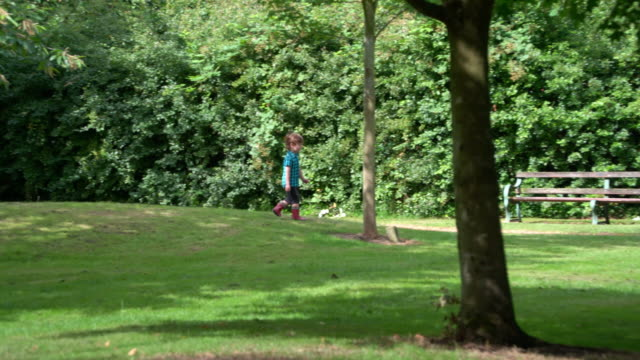boy walking on lawn - ein junge in gummistiefel stock-videos und b-roll-filmmaterial