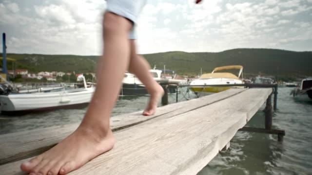 vídeos y material grabado en eventos de stock de boy caminando por el muelle en la playa - amarrado