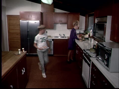 1970 film montage ws boy walking past mother in kitchen with two hot dogs on plate/ cu hand opening microwave and putting plate inside - domestic kitchen stock-videos und b-roll-filmmaterial