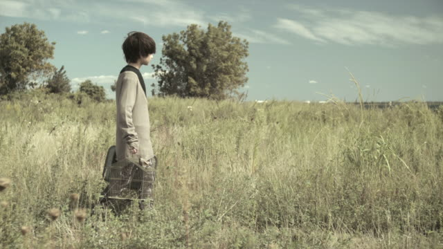 vidéos et rushes de boy walking through a field with birdcage and suitcase, tracking shot - valise