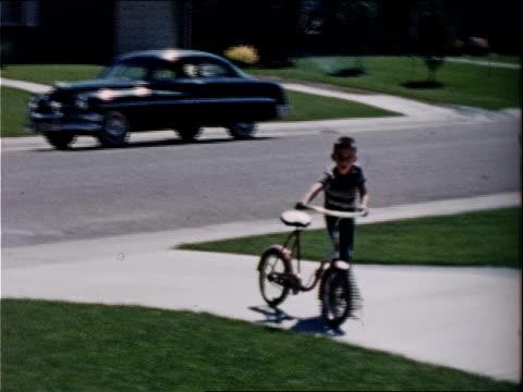 vídeos y material grabado en eventos de stock de a boy walks his bicycle up a driveway. - bicicleta vintage