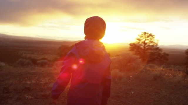 boy walks into sunset after hiking - esplorazione video stock e b–roll