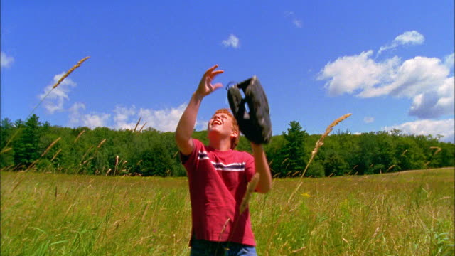 A boy walks through a field while tossing and catching a baseball.